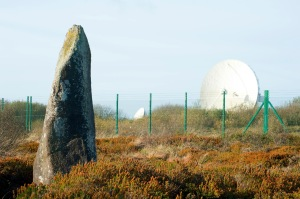 View from the perimeter of large parabolic satellite dishes at the BT Groups Goonhilly Satellite Earth Station on the Lizard Peninsula Cornwall with an upright stone in the foreground